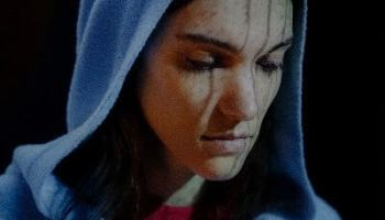 Photo of Charlotte Cardin, a white woman with dark brown hair wearing a blue hoodie and looking down.